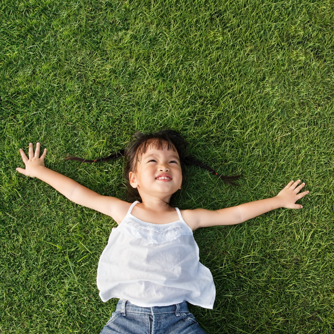 kid laying on the grass smiling
